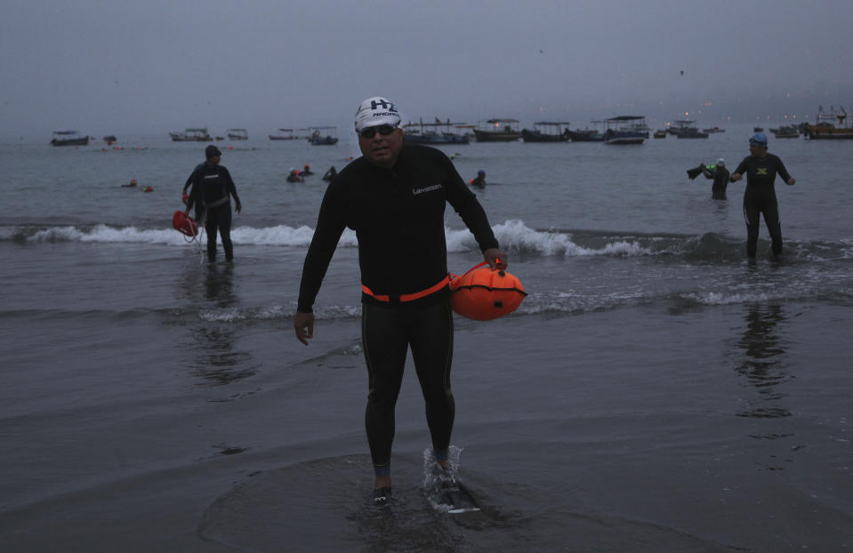 Open water swimmers walk backwards in their flippers, into the sea from Pescadores beach where swimming in the ocean is booming while pools are closed due to the COVID-19 pandemic in Lima, Peru, at sunrise Tuesday, April 27, 2021. One of the few sporting disciplines that have been maintained during the coronavirus pandemic is swimming, which due to the closure of the swimming pools, has moved to the open sea. (AP Photo/Martin Mejia)