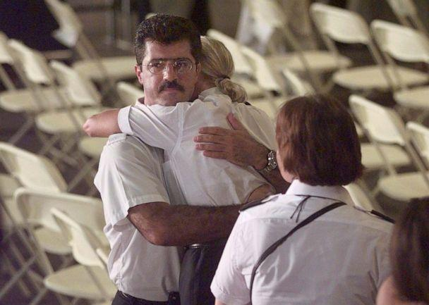 PHOTO: TWA employees embrace following a memorial service for victims of Flight 800 at Hangar 12 in New York's Kennedy Airport, July 16, 1997. (Mark Lennihan/AFP via Getty Images, FILE)