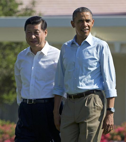President Barack Obama, right, walks with Chinese President Xi Jinping at the Annenberg Retreat at Sunnylands on Saturday, June 8, 2013, in Rancho Mirage, Calif. President Obama and President Xi are retreating to a sprawling desert estate for two days of talks on high-stakes issues, including cybersecurity and North Korea's nuclear threats. (AP Photo/Evan Vucci)
