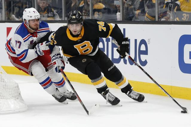 Boston Bruins' Jake DeBrusk (74) handles the puck behind the net while pursued by New York Rangers' Tony DeAngelo (77) during the second period of an NHL hockey game in Boston, Friday, Nov. 29, 2019. (AP Photo/Michael Dwyer)
