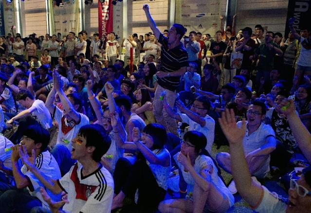 Chinese soccer fans celebrate after Germany won the World Cup, as they watch the final match between Germany and Argentina at the 2nd Live Arena in Beijing, China Monday, July 14, 2014. (AP Photo/Andy Wong)