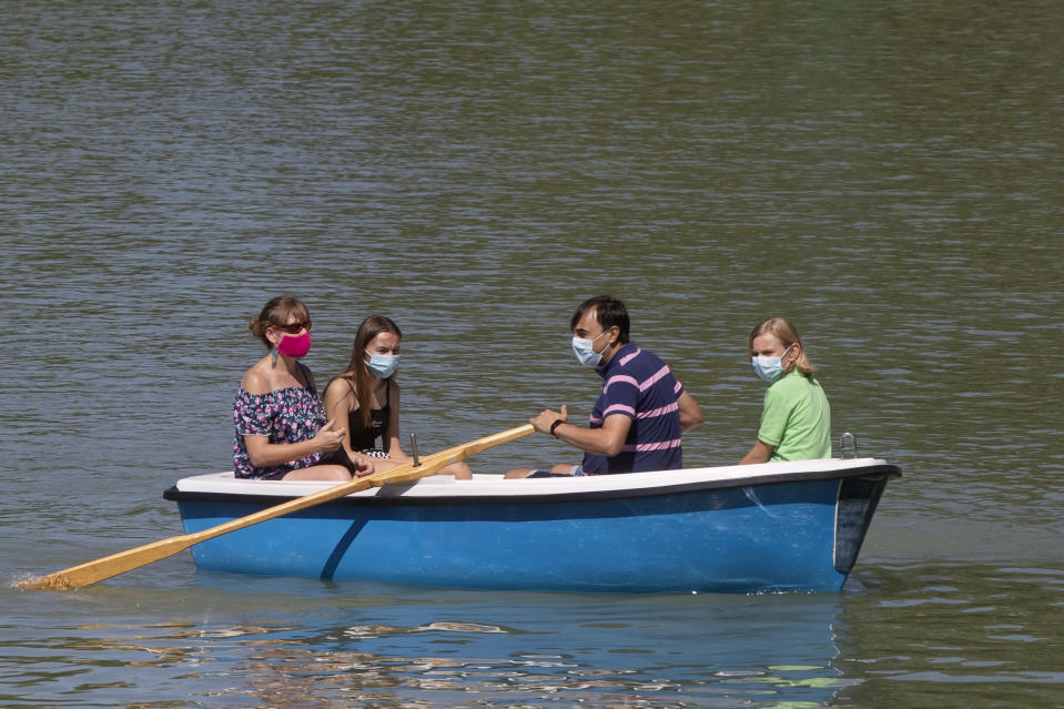 "People wearing protective masks row a pleasure boat in the Retiro park, Madrid, Spain, Sunday, Aug. 23, 2020. Spain's top pandemic expert, Fernando Simon, has warned this week that ""things are not going well"" regarding the increase of infections that the country is seeing. (AP Photo/Paul White)"