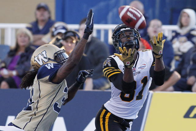 Hamilton Tiger-Cats' Aaron Kelly (81) hauls in a touchdown pass against Winnipeg Blue Bombers' Jeremy McGee (34) during the second half of their pre-season CFL game in Winnipeg Wednesday, June 20, 2012. THE CANADIAN PRESS/John Woods