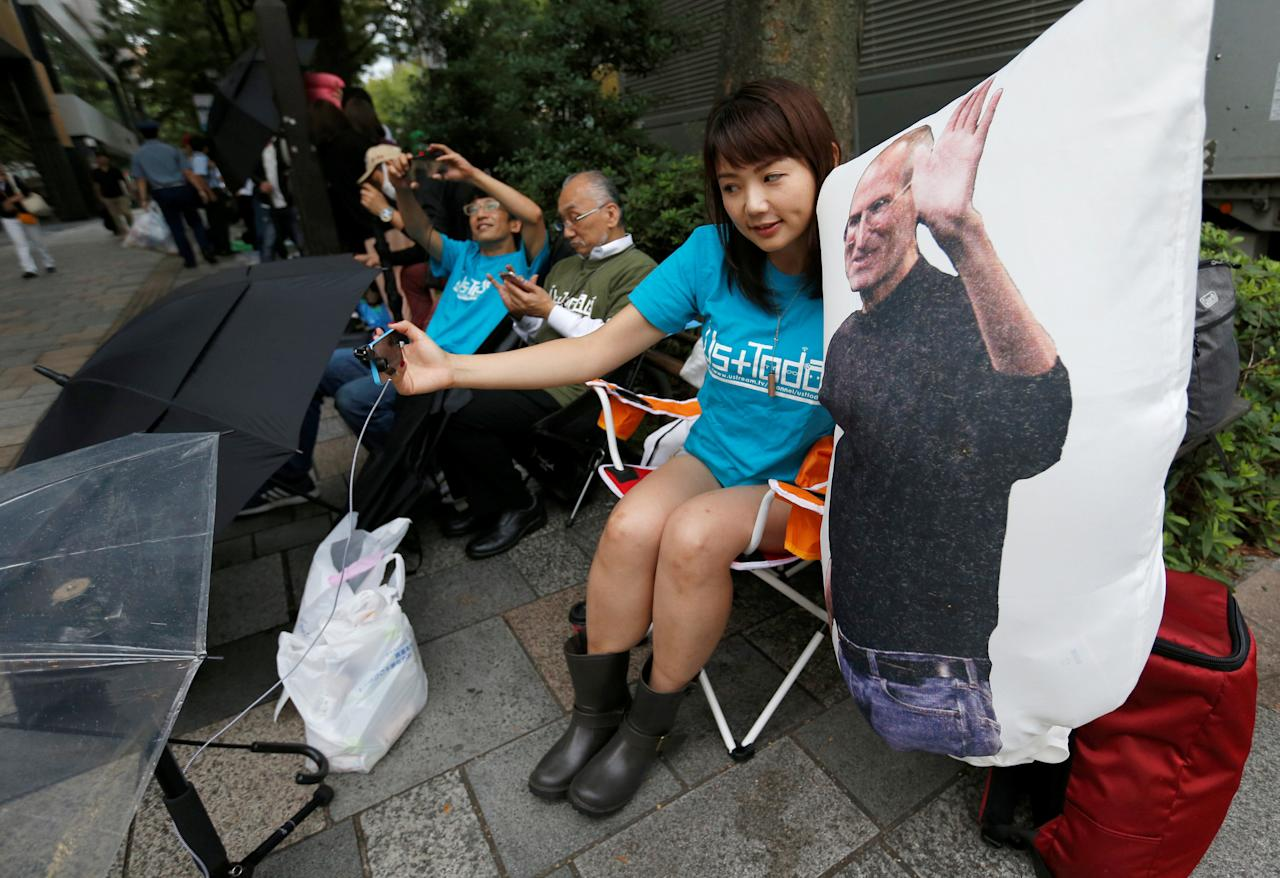 Ayano Tominaga poses with a cushion printed a portrait of Apple co-founder Steve Jobs on it, as she sits in queue for the release of Apple's new iPhone 7 and 7 Plus in front of the Apple Store in Tokyo's Omotesando shopping district, Japan, September 16, 2016.    REUTERS/Issei Kato