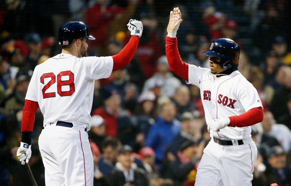Boston Red Sox's Mookie Betts, right, celebrates with J.D. Martinez (28) after scoring on a single by Hanley Ramirez during the first inning of the team's baseball game against the New York Yankees in Boston, Tuesday, April 10, 2018. (AP Photo/Michael Dwyer)