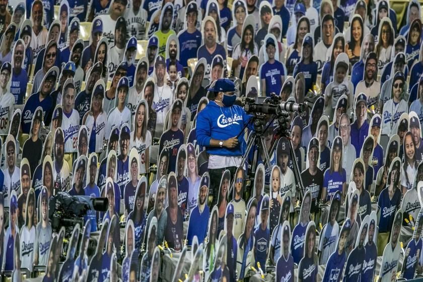 Los Angeles, CA, Thursday, July 23, 2020 - A camera operator works amid a sea of cardboard fans as the LA Dodgers and the San Francisco Giants play the season opener at Dodger Stadium. (Robert Gauthier / Los Angeles Times)