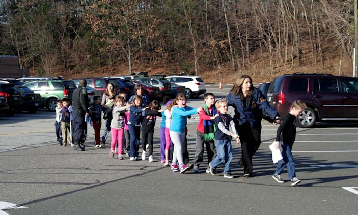 Two Connecticut State Police officers accompany a class of students and two adults out of Sandy Hook Elementary School on Dec. 14, 2012. (Photo: Shannon Hicks/Newtown Bee/Polaris)