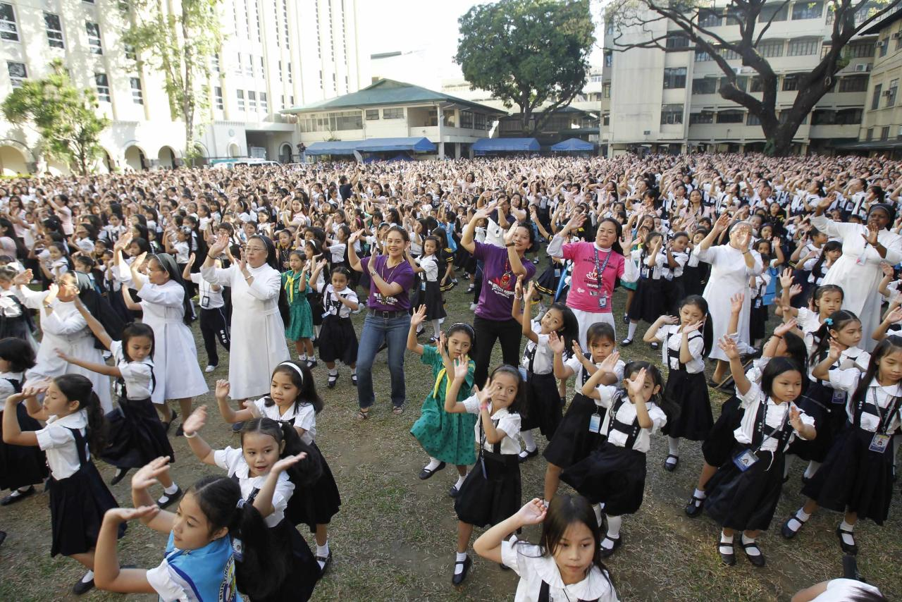 Thousands of students, faculty members and Roman Catholic nuns dance to the theme song of the One Billion Rising campaign in the quadrangle of the St. Scholastica college in Manila February 14, 2013. One Billion Rising is a global campaign to call for an end to violence against women and girls, according to its organisers.  REUTERS/Romeo Ranoco (PHILIPPINES - Tags: POLITICS SOCIETY EDUCATION RELIGION)