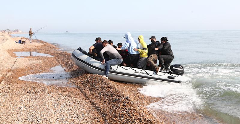 A group of people thought to be migrants arrive in an inflatable boat at Kingsdown beach, near Dover, Kent, after crossing the English Channel.