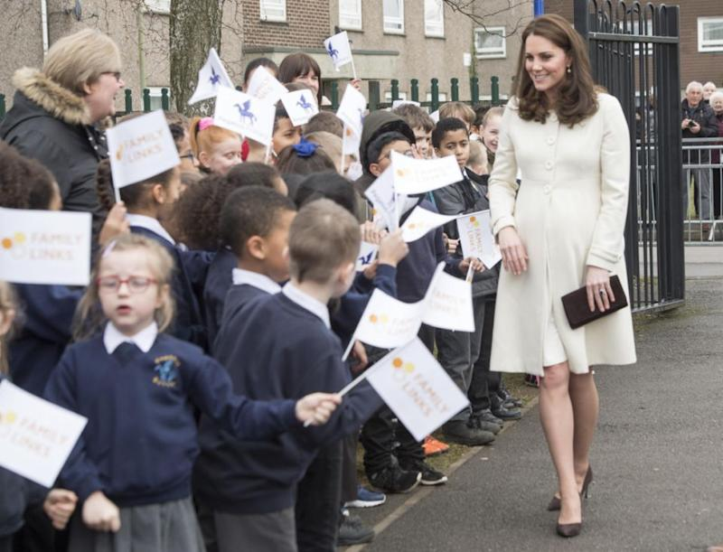 She was greeted at the school gates by a swarm of flag-bearing kids. Photo: Getty Images