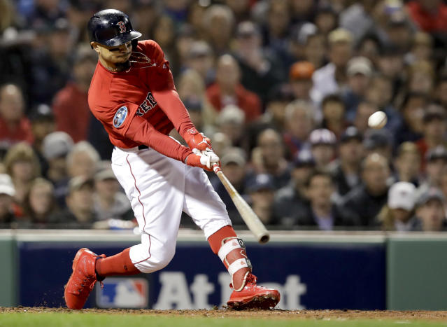 Boston Red Sox's Mookie Betts hits a double against the New York Yankees during the third inning of Game 1 of a baseball American League Division Series on Friday, Oct. 5, 2018, in Boston. (AP Photo/Charles Krupa)