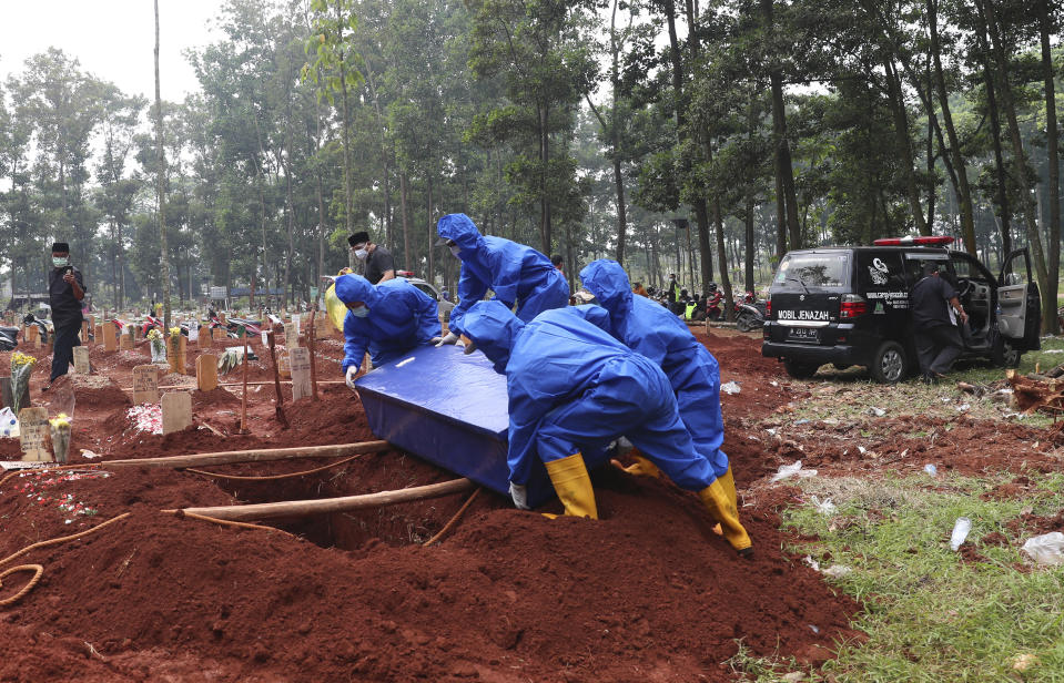 Workers in protective suits carry a coffin containing the body of a COVID-19 victim to a grave for a burial at Cipenjo cemetery in Bogor, West Java, Indonesia, Wednesday, July 14, 2021. (AP Photo/Achmad Ibrahim)