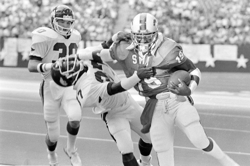 Running back Eric Dickerson (19) of Southern Methodist pushes his way past Nathan Jones (37) of the Arkansas Razorbacks in the second quarter at Texas Stadium in Irving, Texas, Nov. 20, 1982. Dickerson gained 12 yards on the play, moving the ball to the 17-yard line and setting up an SMU touchdown. (AP Photo/David Breslauer)