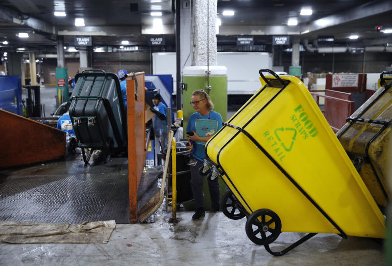 In this March 26, 2019, photo, people work in a recycling area in the back of the house at the Palazzo casino-resort in Las Vegas. The Venetian and Palazzo casino-resorts, which are operated by Las Vegas Sands, send their food scraps to the Las Vegas Livestock pig farm 25 miles north of the Strip. (AP Photo/John Locher)