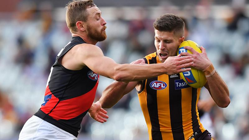 Essendon's Devon Smith lays a tackle on Hawthorn opponent Luke Breust. (Photo by Mark Brake/Getty Images)