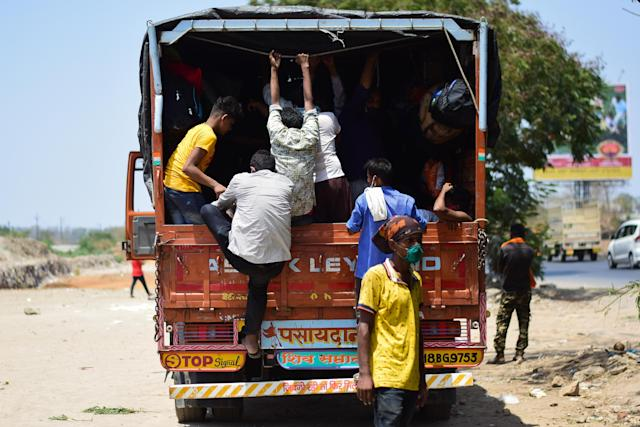 MUMBAI, MAHARASHTRA, INDIA - 2020/05/13: People getting onto a truck during the lockdown. Due to lockdown situation, most migrants are stuck in Mumbai, some walk and others arrange their own trucks and buses to their home towns, while the police say that the buses are available by the government. (Photo by Ratika More/SOPA Images/LightRocket via Getty Images)