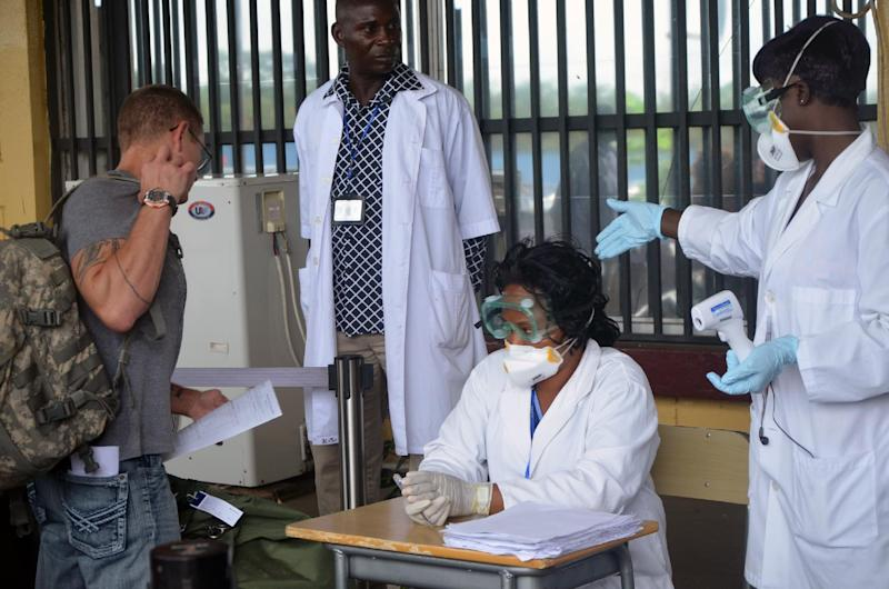 Health agents check a passenger leaving Liberia at the Roberts International Airport near Monrovia, on Agust 27, 2014 (AFP Photo/Zoom Dosso)