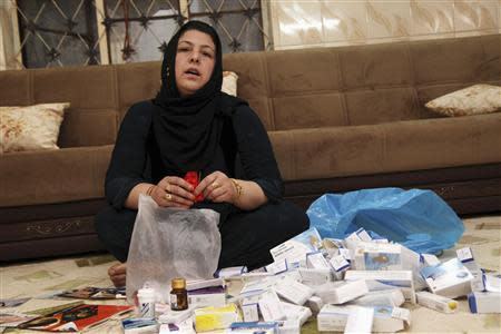 Hamida Hassan Mohammed one of victims of the 1988 chemical attack on Halabja, empties a bag of medicine in her home in Halabja