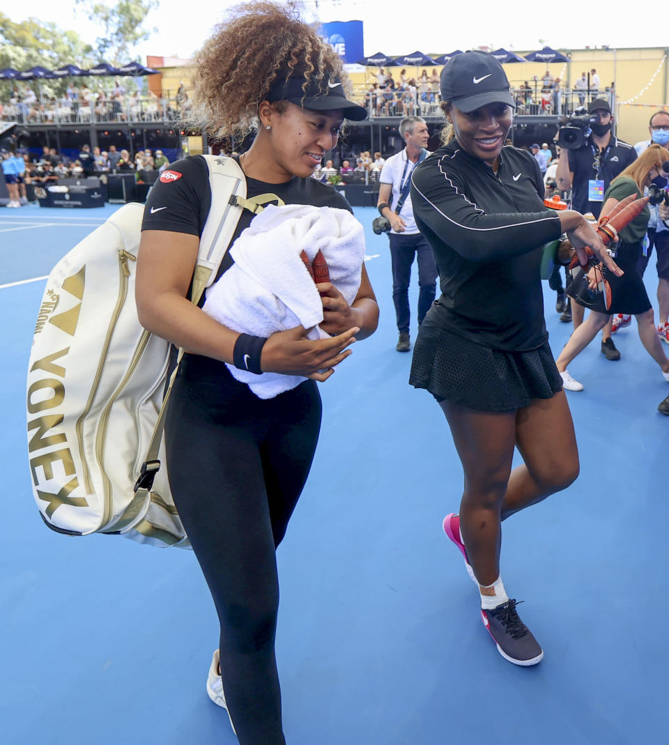 Naomi Osaka, left, of Japan and Serena Williams of the U.S. walk from the court together following an exhibition tennis event in Adelaide, Australia, Friday, Jan 29. 2021. (Kelly Barnes/AAP Image via AP)
