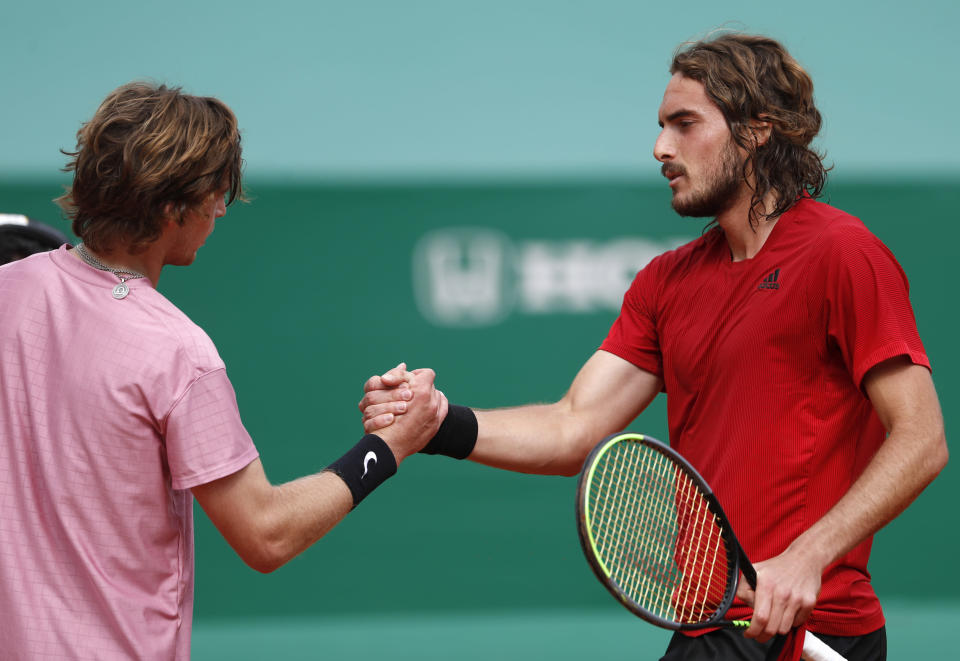 Stefanos Tsitsipas, right, of Greece shake hands with Andrey Rublev of Russia after winning the Monte Carlo Tennis Masters tournament finals in Monaco, Sunday, April 18, 2021. (AP Photo/Jean-Francois Badias)