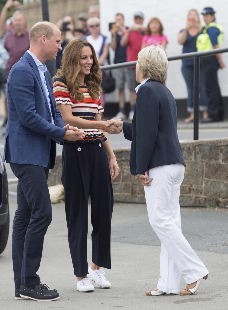 Dressed in a chic pair of wide-leg trousers and a colorful striped top, the stylish royal completed her nautical look with her favorite summer sneakers. (Photo: Getty Images)