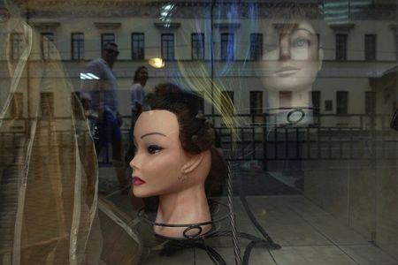Passers-by are reflected in the window of a hair salon in Nizhny Novgorod, Russia, June 30, 2018. REUTERS/Damir Sagolj