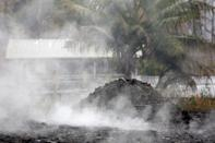 Volcanic gases rise from the ground in a yard in Leilani Estates during ongoing eruptions of the Kilauea Volcano in Hawaii, U.S., May 18, 2018. REUTERS/Terray Sylvester