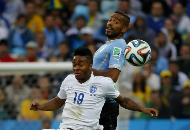 England's Raheem Sterling (front) and Uruguay's Alvaro Pereira jump for the ball during their 2014 World Cup Group D soccer match at the Corinthians arena in Sao Paulo June 19, 2014. REUTERS/Laszlo Balogh (BRAZIL - Tags: SOCCER SPORT WORLD CUP)