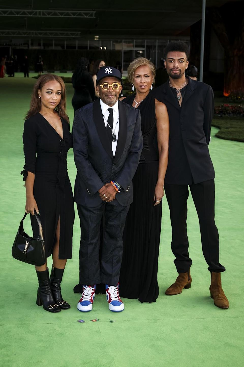 A family of four posing in black formal attire on a green carpet