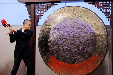 FILE PHOTO: Wang Xing, co-founder, chairman and chief executive officer of China's Meituan Dianping hits the gong during the debut of the company at the Hong Kong Exchanges in Hong Kong, China September 20, 2018. REUTERS/Tyrone Siu/File Photo