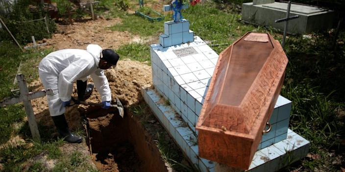 A gravedigger wears protective clothing as he buries a COVID-19 victim at Recanto da Paz, a cemetery in Breves, Marajo island, Brazil, on June 7, 2020.