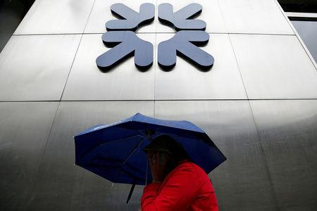 FILE PHOTO: FILE PHOTO: A woman shelters under an umbrella as she walks past a branch of RBS in the City of London