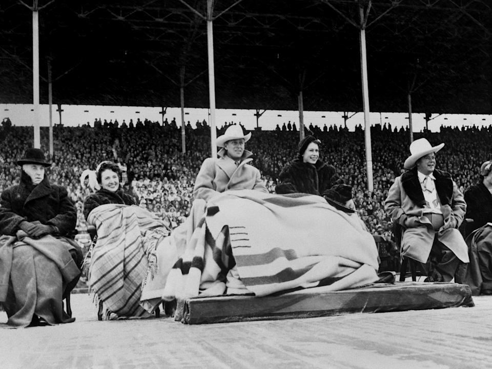 Princess Elizabeth and the Duke of Edinburgh wearing a blanket (a wedding present from Canada) watching the the Calgary Stampede during their 1951 visit. (Photo: PA Images via Getty Images)