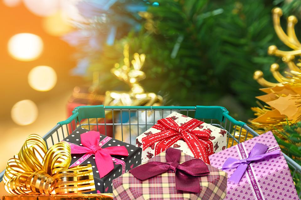 Christmas gifts and presents in shopping trolley with christmas decorations and blurred lights on christmas tree background.
