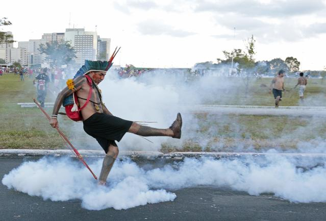 A native Brazilian kicks a tear gas grenade back at riot police blocking a group of Indians from approaching the Mane Garrincha soccer stadium in Brasilia May 27, 2014. Police fired tear gas canisters to contain anti-World Cup demonstrators who tried to march to the Brasilia stadium where the soccer tournament's trophy was on public display on Tuesday. REUTERS/Joedson Alves (BRAZIL - Tags: SPORT SOCCER WORLD CUP CIVIL UNREST POLITICS)