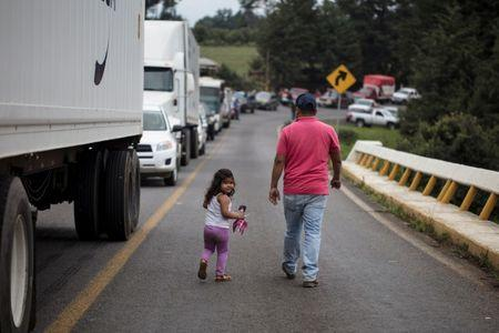 People walk along a blockade by members of the Supreme Indigenous Council of the entry to their community to avoid the installation of polling stations for Mexico's general election in the indigenous Purepecha town of Zirahuen, in Michoacan state, Mexico June 28, 2018. Picture taken June 28, 2018. REUTERS/Alan Ortega