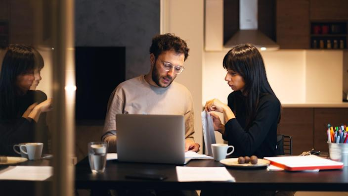 Young couple is sitting at the table with laptop and paying bills online.