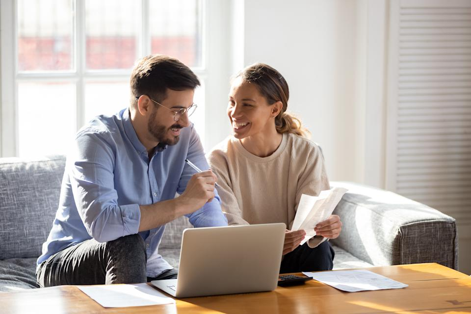 Happy young married couple sit on couch calculate expenses use easy online banking service at home, smiling millennial husband and wife count taxes house expenditures pay bills on internet