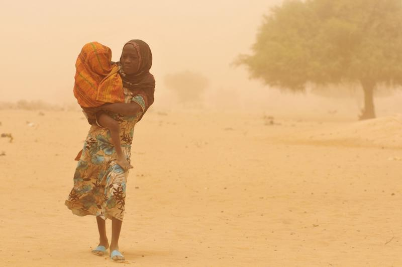 A girl carries her baby sibling through a haze of dust in Sidi Village, in Kanem Region. She is taking him to be screened for malnutrition at a mobile outpatient centre for children, operated by one nurse and four nutrition workers. The programme is new to the area. Several months ago, most children suffering from severe malnutrition had to be transported to health centres in the town of Mundo, 12 kilometres away, or in the city of Mao, some 35 kilometres away. In April 2010 in Chad, droughts have devastated local agriculture, causing chronic food shortages and leaving 2million people in urgent need of food aid. Due to poor rainfall and low agricultural yields, malnutrition rates have hovered above emergency thresholds for a decade. But the 2009 harvest was especially poor, with the production of staple crops declining by 20 percent to 30 percent. Food stocks have since dwindled, and around 30 percent of cattle in the region have died from lack of vegetation.