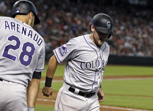 Colorado Rockies' Garrett Hampson, right, is congratulated by teammate Nolan Arenado (28) after scoring a run against the Arizona Diamondbacks during the fifth inning of a baseball game, Saturday, July 21, 2018, in Phoenix. (AP Photo/Ralph Freso)