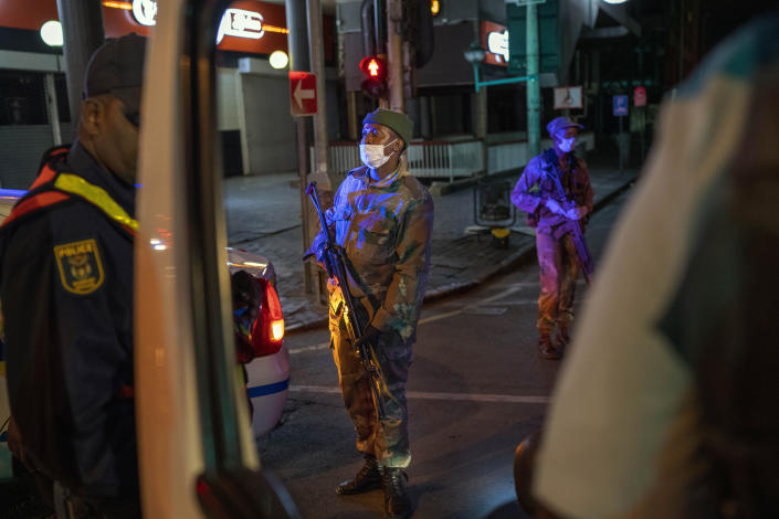 South African Defense Forces and police check a minibus driver who violated the lockdown downtown Johannesburg, South Africa, Friday, March 27, 2020. Police and army started patrolling moments after South Africa went into a nationwide lockdown for 21 days in an effort to mitigate the spread to the coronavirus. The new coronavirus causes mild or moderate symptoms for most people, but for some, especially older adults and people with existing health problems, it can cause more severe illness or death.(AP Photo/Jerome Delay)