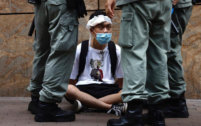 Riot police guard detain a protester as a second reading of a controversial national anthem law takes place in Hong Kong, Wednesday, May 27, 2020