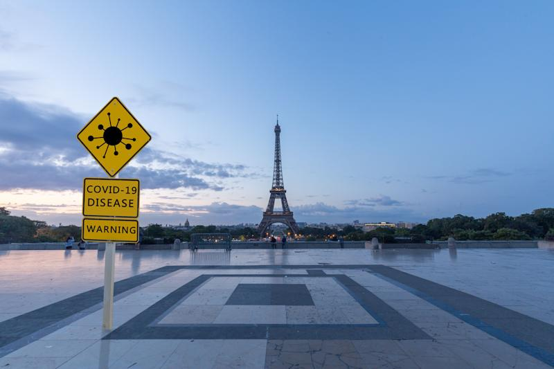 covid-19 warning sign with Eiffel tower,Paris (Photo: lupengyu via Getty Images)