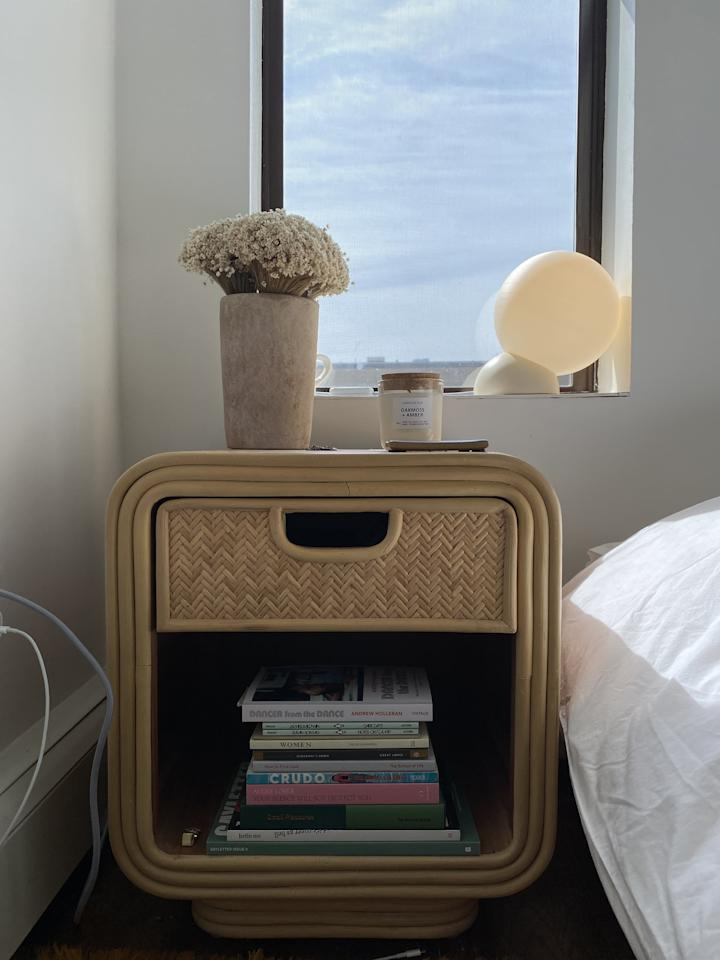 """<p>I want my bedroom to feel light and airy, which means being sparse about furniture. I chose the chic <a href=""""https://www.popsugar.com/buy/Ria-Nightstand-577869?p_name=Ria%20Nightstand&retailer=urbanoutfitters.com&pid=577869&price=199&evar1=casa%3Aus&evar9=47505185&evar98=https%3A%2F%2Fwww.popsugar.com%2Fhome%2Fphoto-gallery%2F47505185%2Fimage%2F47507310%2FBreezy-Bedside-Details&list1=home%20decorating%2Cinterior%20design%2Cdecor%20inspiration&prop13=api&pdata=1"""" rel=""""nofollow"""" data-shoppable-link=""""1"""" target=""""_blank"""" class=""""ga-track"""" data-ga-category=""""Related"""" data-ga-label=""""https://www.urbanoutfitters.com/shop/ria-nightstand"""" data-ga-action=""""In-Line Links"""">Ria Nightstand</a> ($199) for the look of its '70s-callback rounded edges, the bamboo tone, and the woven rattan drawer. Plus, it's nice to have some of your favorite books at arm's length. On my shelf is <a href=""""https://www.theschooloflife.com/shop/us/tsol-press-small-pleasures-book/"""" target=""""_blank"""" class=""""ga-track"""" data-ga-category=""""Related"""" data-ga-label=""""https://www.theschooloflife.com/shop/us/tsol-press-small-pleasures-book/"""" data-ga-action=""""In-Line Links""""><strong>Small Pleasures</strong></a> by The School of Life, along with favorites from <a href=""""https://donlonbooks.com/"""" target=""""_blank"""" class=""""ga-track"""" data-ga-category=""""Related"""" data-ga-label=""""https://donlonbooks.com/"""" data-ga-action=""""In-Line Links"""">Donlon Books</a> like <strong>Women</strong> by Chloe Caldwell and <strong>Crudo: A Novel</strong> by Olivia Laing. (This <a href=""""https://www.popsugar.com/buy/Ria-Magazine-Holder-578159?p_name=Ria%20Magazine%20Holder&retailer=urbanoutfitters.com&pid=578159&price=49&evar1=casa%3Aus&evar9=47505185&evar98=https%3A%2F%2Fwww.popsugar.com%2Fhome%2Fphoto-gallery%2F47505185%2Fimage%2F47507310%2FBreezy-Bedside-Details&list1=home%20decorating%2Cinterior%20design%2Cdecor%20inspiration&prop13=api&pdata=1"""" rel=""""nofollow"""" data-shoppable-link=""""1"""" target=""""_blank"""" class=""""ga-track"""" data-ga-category=""""Related"""" data-ga-lab"""