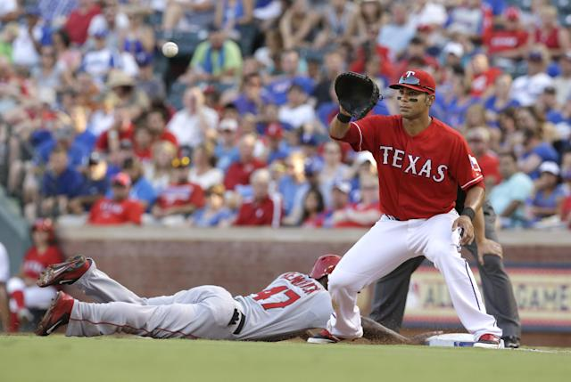 Los Angeles Angels Howie Kendrick, left, dives back to base beating the pick off throw to Texas Rangers first baseman Carlos Pena (21) during the fourth inning of a baseball in Arlington, Texas, Saturday, July 12, 2014. (AP Photo/LM Otero)