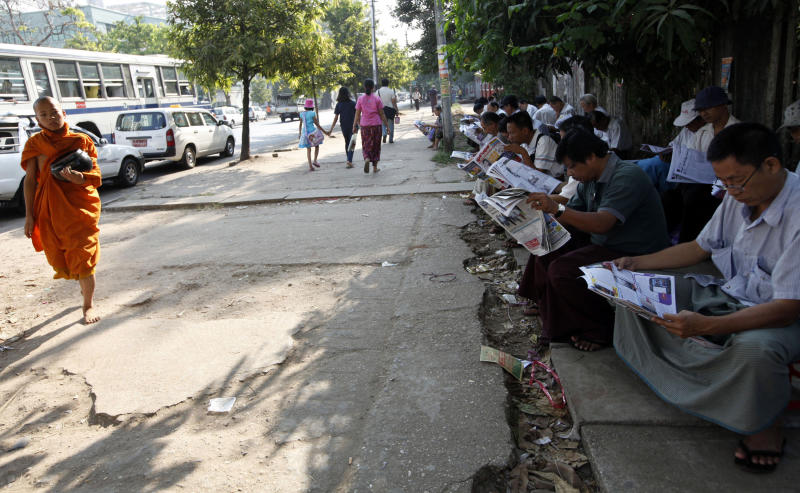 People read state-run newspaper or weekly journals on a street in Yangon, Myanmar, Tuesday, March 12, 2013. An eagerly awaited official report has confirmed that police in Myanmar used smoke bombs that contain phosphorus during a crackdown on anti-mine protesters last year that left 108 people with burns, mostly Buddhist monks. The report also recommended the controversial Chinese-backed project continue. (AP Photo/Khin Maung Win)