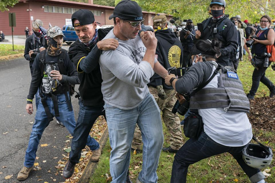 A member of the Proud Boys tackles a fellow member after he assaulted freelance journalist during a Proud Boy rally on September 26, 2020 in Portland, Oregon  (Getty Images)