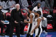 San Antonio Spurs head coach Gregg Popovich, left, talks to Devin Vassell, center, during the first half of an NBA basketball game against the Brooklyn Nets Wednesday, May 12, 2021, in New York. (AP Photo/Frank Franklin II)