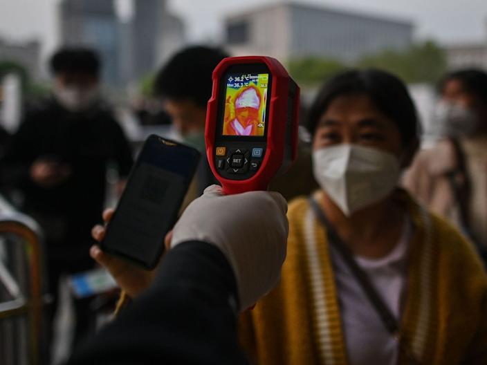A worker controls the temperature of a woman as she arrives at Hankou Railway Station in Wuhan on April 8, 2020.