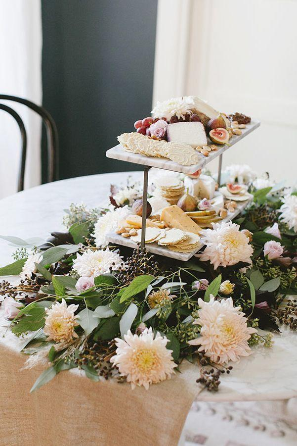 """<p>Work your appetizer spread into your centerpiece, so everyone can keep snacking—even after the dishes are cleared away. And while we're partial to chrysanthemums, feel free to mix in your favorites fall flowers.</p><p><strong>Get the tutorial at </strong><a href=""""https://jojotastic.com/2017/11/16/a-non-traditional-blush-thanksgiving-centerpiece-diy/"""" rel=""""nofollow noopener"""" target=""""_blank"""" data-ylk=""""slk:Jojotastic"""" class=""""link rapid-noclick-resp""""><strong>Jojotastic</strong></a><strong>.</strong></p><p><a class=""""link rapid-noclick-resp"""" href=""""https://www.amazon.com/Tier-Collapsible-Sturdier-Plate-Stand/dp/B01IU5OTSU/?tag=syn-yahoo-20&ascsubtag=%5Bartid%7C10050.g.2130%5Bsrc%7Cyahoo-us"""" rel=""""nofollow noopener"""" target=""""_blank"""" data-ylk=""""slk:SHOP SERVING PLATES""""><strong>SHOP SERVING PLATES</strong></a></p>"""